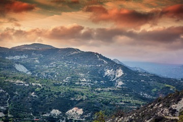 Beautiful sunset in the mountains, Cyprus, Troodos. Green hills, flowering trees and bright sunset colors