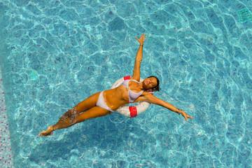 Beautiful tanned woman in blue swimwear relaxing in pool spa.