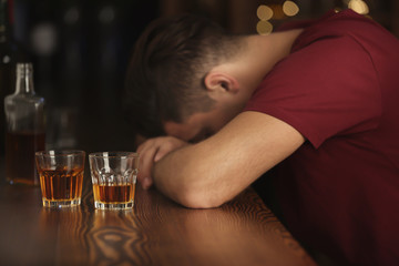 Unconscious drunk man with glasses of drink in bar. Alcoholism problem