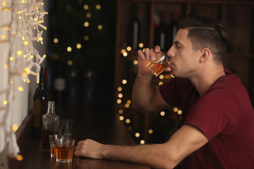 Young man drinking alcohol in bar