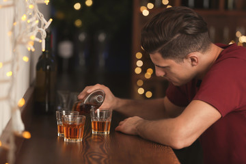 Young man pouring drink into glass at bar. Alcoholism problem