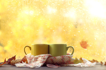 autumn break with mood/ two mugs in a pink scarf on a table strewn with leaves against a window with drops after a rain