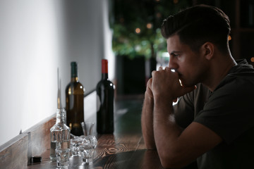 Young man sitting at table in bar. Alcoholism problem