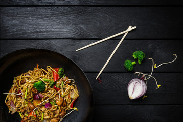 Stir fry noodles in traditional Chinese wok, chopsticks and ingredients. Space for text.