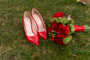 Female fashion red wedding shoes with golden rings on them in focus and bride's bouquet with red roses and green berries out of focus on green grass background.