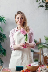 Picture of florist woman in apron at room with flowers