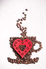 Valentine Heart shape made from coffee beans on wooden surface.