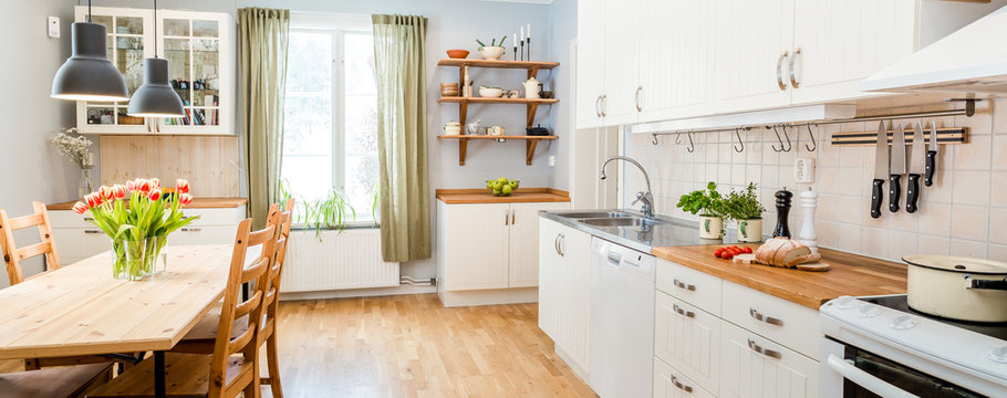 banner of a kitchen with kitchen table  and breakfast at the kitchen counter top white cupboards and wooden floor