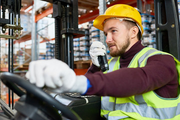 Waist up portrait of young man sitting in forklift and using walkie-talkie while moving goods in warehouse, copy space