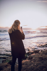 Young woman taking picture with her smartphone of breathtaking sunset at the beach