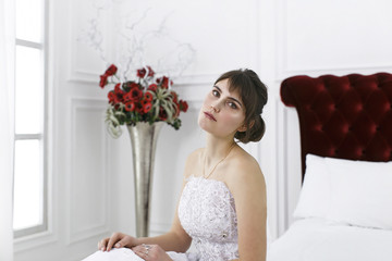 Young beautiful girl in a bride's dress sits on the edge of the bed