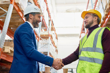 Waist up portrait of handsome mature businessman shaking hands with worker wearing hardhat standing against warehouse shelves in background
