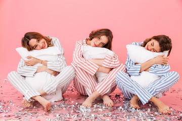 Photo of sleepy women 20s wearing leisure clothings holding pillows and taking pleasure during slumber party, isolated over pink background