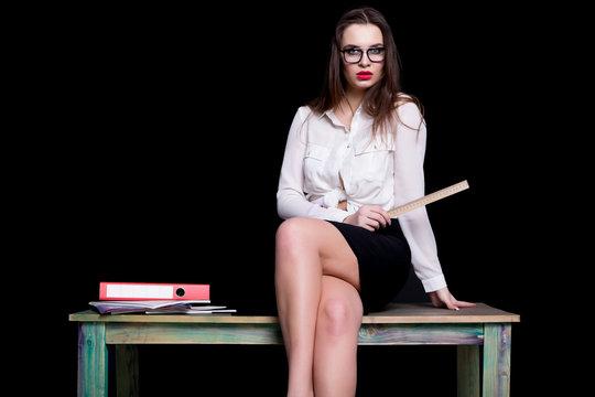 sexy teacher posing on desk in studio on black background