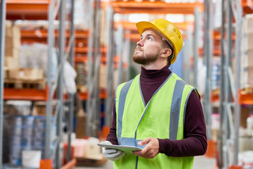 Waist up portrait of modern warehouse worker using digital tablet looking up at tall shelves, copy space