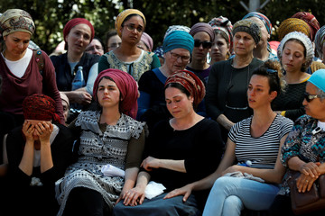 Ayelet Coleman (3rd R), wife of Adiel Coleman, an Israeli who was killed in a stabbing attack in Jerusalem's Old City on March 18, mourns during his funeral in the Jewish settlement of Kochav Hashchar in the Israeli occupied West Bank