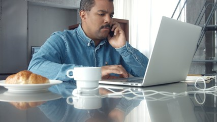 mixed race adult man working in studio with notebook On the table are cup of coffee, croissant. Morning work