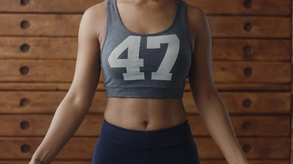 african american woman makes a jump rope routine in sunny loft for healthy life. body closeup front view
