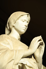 Old statue of a woman praying inside the monumental cemetery of the Certosa di Bologna. The public cemetery was established in 1801.