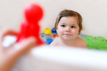 Cute adorable baby girl taking foamy bath in bathtub. Toddler playing with bath rubber toys.