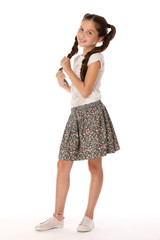A little girl 12 years old posing in summer clothes. Charming pretty slender young teenager is in a skirt with bare legs. Beautiful brunette child is standing at full length and smiles slightly.