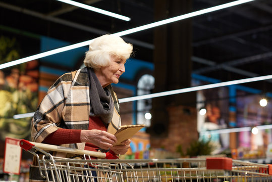 Portrait of modern senior woman  grocery shopping in supermarket pulling shopping cart and smiling, copy space