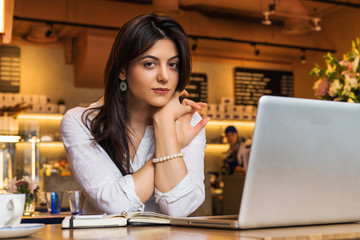 Portrait of young businesswoman. Girl works remotely on laptop in restaurant. Online marketing, education, e-learning.