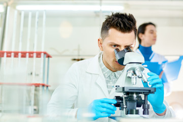 Handsome young scientist with stylish haircut using microscope while working on ambitious project, interior of modern laboratory on background