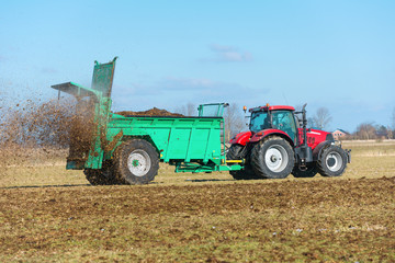 Tractor with manure spreader on the field - 1292