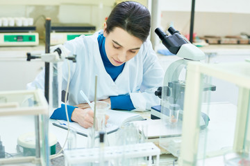 Beautiful dark-haired researcher wearing white coat sitting at desk and taking notes after successful completion of scientific experiment, interior of modern laboratory on background