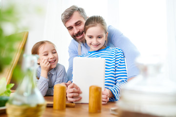 Waist up portrait of happy bearded father playing with two daughters at home, using digital tablet and smiling, copy space