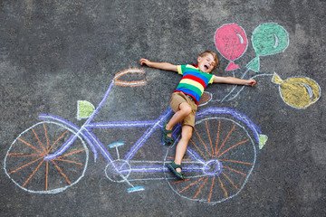 little kid boy having fun with bike chalks picture