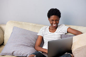 beautiful woman smiling and using laptop on couch at home