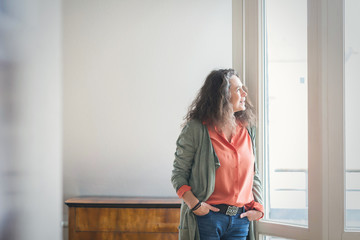 Trendy attractive mature woman in jeans standing with hands in pockets staring out of a large bright window with lateral copy space
