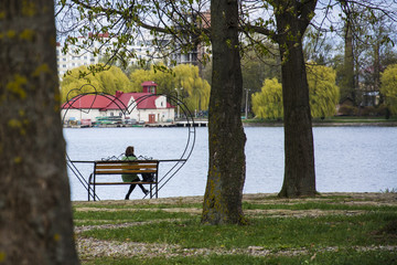 Lonely woman sitting alone on a bench in a pack near the lake