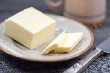 Piece of butter on plate with knife. Background and shallow focus.