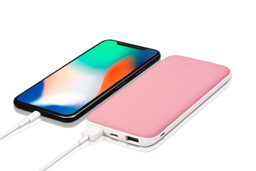 Perfect combo view of  soft pink and white power bank attached with smartphone through white color data cable wire to charge your phone fast and safe.