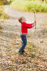 A small boy  a selfie-stick with smartphone and monopod in autumn park, and photographing himselves smiling on a background autumn forest