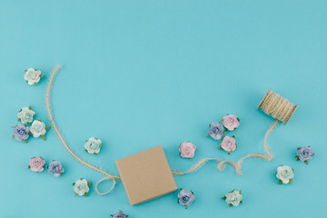 Brown box and rope decorate with blue tone paper flowers and ribbon on pastel blue background with copy space