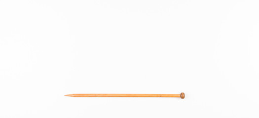 Wooden knitting needle on white background.