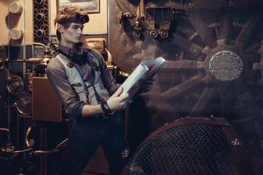 Portrait of a young mad scientist traveler in a steampunk style suit with a card.