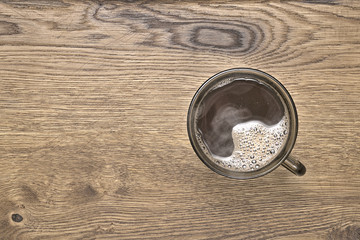 brown mug with hot coffee on wood background