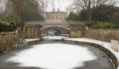 Kennet and Avon Canal frozen in Bath. Iced formed on surface of waterway by Sydney Gardens, running through centre of World Heritage City in Somerset, UK