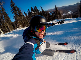Guy sportsman goes on normal skiing on ski slope with action camera. Sunset. Sheregesh, Kemerovo region, Russia.