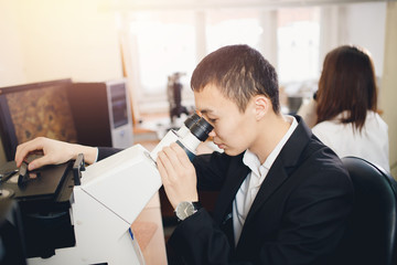 Materials Science. A young male student is sitting at a microscope.