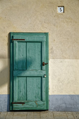 Ancient door in green color, cracked wooden entrance, sample for post card