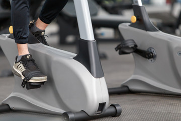 Close-up footage of a man working out in gym on the exercise bike, young man cycling in the gym. female exercising in fitness gym for good health.
