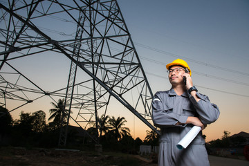 An electrical engineer wearing yellow hard hat speak on mobile phone and hold blueprint close to electricity power pole