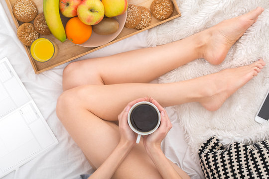 Young woman sitting on bed leisure concept holding cup of hot americano