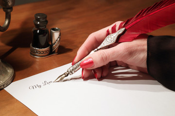 A woman's hand writes a letter with a quill in the candle light